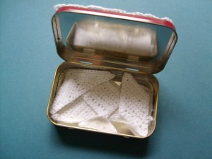 The crocheted tangrams fitting in the Altoids tin